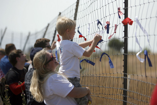 Francisco Kjolseth     The Salt Lake Tribune Red, white and blue ribbons are tied to the outer perimeter fence of the new NSA Data Center as opponents of the facility protest on the 4th of July.