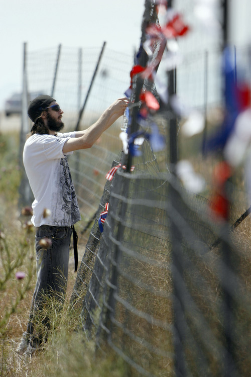 Francisco Kjolseth  |  The Salt Lake Tribune Brandon Otterstron of Clearfield ties a ribbon on the outer most perimeter fence of the new NSA Data Center along Redwood road across from Camp Williams as he joins other opponents of the new facility on the 4th of July.