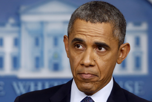 """President Barack Obama listens while speaking about the the budget and the partial government shutdown, Tuesday, Oct. 8, 2013, in the Brady Press Room of the White House in Washington. The president said he told House Speaker John Boehner he's willing to negotiate with Republicans on their priorities, but not under the threat of """"economic chaos.""""  (AP Photo/Charles Dharapak)"""