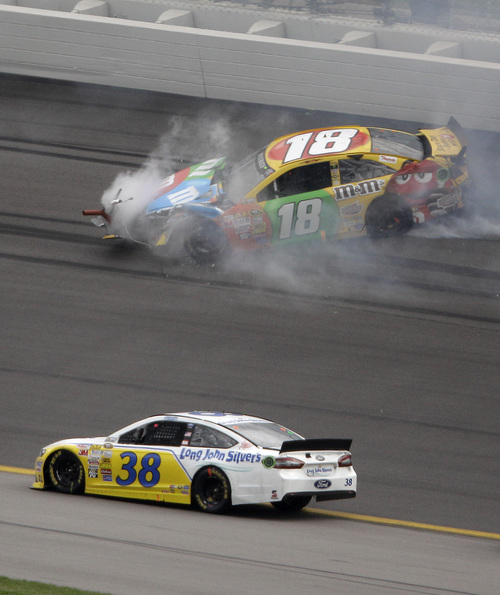 David Gilliland (38) drives past Kyle Busch's wrecked car during a NASCAR Sprint Cup series auto race at Kansas Speedway in Kansas City, Kan., Sunday, Oct. 6, 2013. (AP Photo/Charlie Riedel)