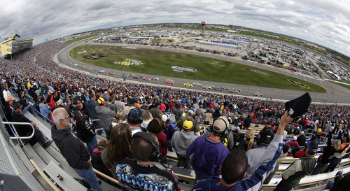 Fans cheer as drivers resume racing after a caution during a NASCAR Sprint Cup series auto race at Kansas Speedway in Kansas City, Kan., Sunday, Oct. 6, 2013. (AP Photo/Charlie Riedel)