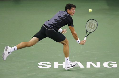 Milos Raonic of Canada returns a ball to Michal Przysiezny of Poland during their singles match at the Shanghai Masters tennis tournament at Qizhong Forest Sports City Tennis Center, in Shanghai, China, Tuesday, Oct. 8, 2013. Raonic won the match 6-4, 6-4. (AP Photo/Eugene Hoshiko)