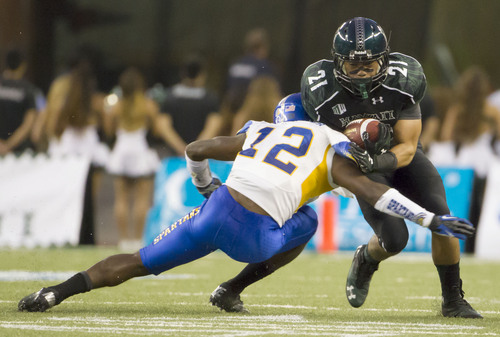 San Jose State cornerback Forrest Hightower (12) tackles Hawaii running back Samson Anguay (21) in the first quarter of an NCAA college football game Saturday, Oct. 5, 2013, in Honolulu. (AP Photo/Eugene Tanner)