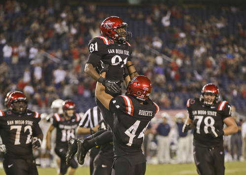 San Diego State wide receiver Eric Judge is lifted by Adam Roberts after his thirteen yard touchdown reception in overtime against Nevada that proved to be the winning score in San Diego State's 51-44 victory in a NCAA college football game  Friday, Oct. 4, 2013, in San Diego. (AP Photo/Lenny Ignelzi)