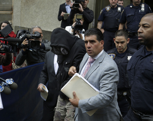 Wojciech Braszczok, center left, with face covered, leaves the courthouse in New York, Wednesday, Oct. 9, 2013. Braszczok, an undercover police detective, was charged with gang assault in a motorcycle rally that descended into violence in New York. (AP Photo/Seth Wenig)