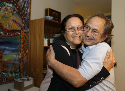Stanford University professor Michael Levitt, who won the Nobel Prize in chemistry, is embraced by his wife Rina at their home on Wednesday, Oct. 9, 2013, in Stanford, Calif. Three U.S.-based scientists won this year's Nobel Prize in chemistry for developing powerful computer models that researchers use to understand complex chemical interactions and create new drugs. Research in the 1970s by Levitt, Martin Karplus and Arieh Warshel led to programs that unveil chemical processes such as how exhaust fumes are purified or how photosynthesis takes place in green leaves. (AP Photo/Eric Risberg)