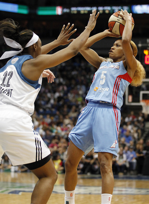 Atlanta Dream guard Jasmine Thomas (5) goes for a shot against Minnesota Lynx guard Monica Wright (22) during the first half of Game 2 of the WNBA basketball finals, Tuesday, Oct. 8, 2013, in Minneapolis. (AP Photo/Stacy Bengs)