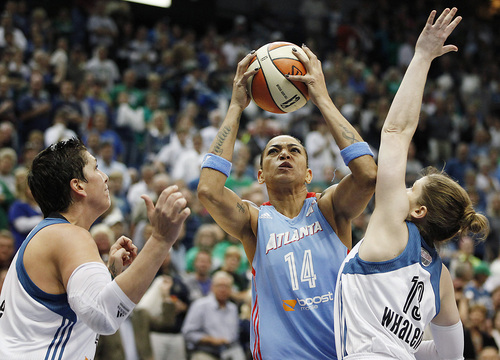 Atlanta Dream forward Erika de Souza (14) lines up a shot against Minnesota Lynx forward Janel McCarville, left, and guard Lindsay Whalen during Game 2 of the WNBA basketball finals, Tuesday, Oct. 8, 2013, in Minneapolis. (AP Photo/Stacy Bengs)
