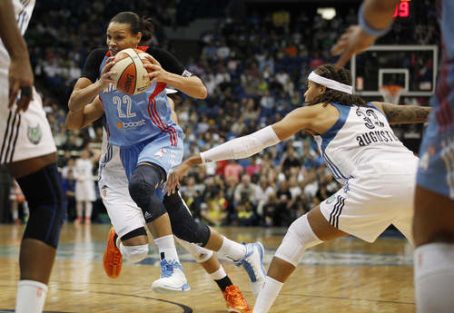 Atlanta Dream guard Armintie Herrington (22) pushes the ball past Minnesota Lynx guard Seimone Augustus (33) during the first half of Game 2 of the WNBA basketball finals, Tuesday, Oct. 8, 2013, in Minneapolis. (AP Photo/Stacy Bengs)