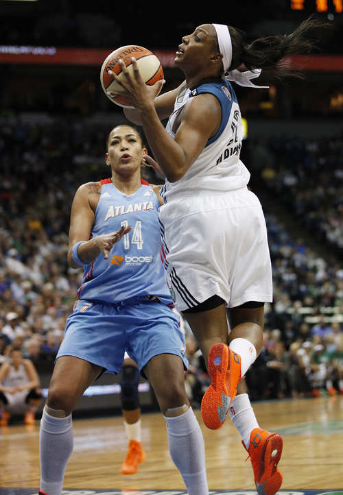 Minnesota Lynx guard Monica Wright (22) looks back to shoot against Atlanta Dream forward Erika de Souza (14) during the second half of Game 2 of the WNBA basketball finals, Tuesday, Oct. 8, 2013, in Minneapolis. The Lynx won 88-63. (AP Photo/Stacy Bengs)