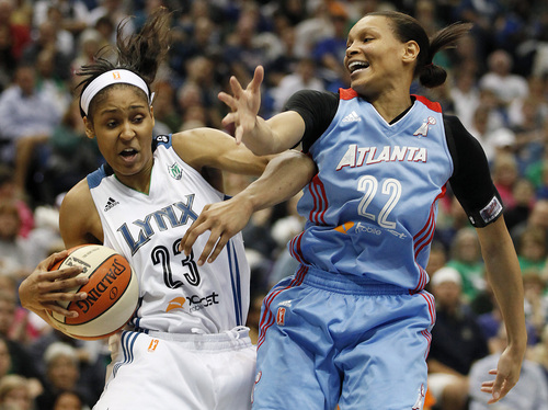 Minnesota Lynx forward Maya Moore (23) protects a rebound ball against Atlanta Dream guard Armintie Herrington (22) during the first half of Game 2 of the WNBA basketball finals, Tuesday, Oct. 8, 2013, in Minneapolis. (AP Photo/Stacy Bengs)