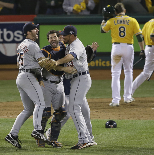 From front left to right, Detroit Tigers pitcher Justin Verlander, catcher Alex Avila and pitcher Joaquin Benoit celebrate after the final out of the ninth inning of Game 5 of an American League baseball division series against the Oakland Athletics in Oakland, Calif., Thursday, Oct. 10, 2013. The Tigers won 3-0.  Athletics' Jed Lowrie (8) walks away. (AP Photo/Jeff Chiu)