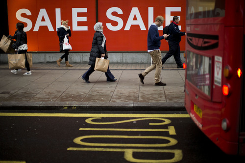 FILE - In this Monday, Dec. 24, 2012, file photo, people walk past sale signs on Oxford Street in London.  The British spent 3 percent less in 2012 than they did five years earlier, in 2007. (AP Photo/Matt Dunham, File)