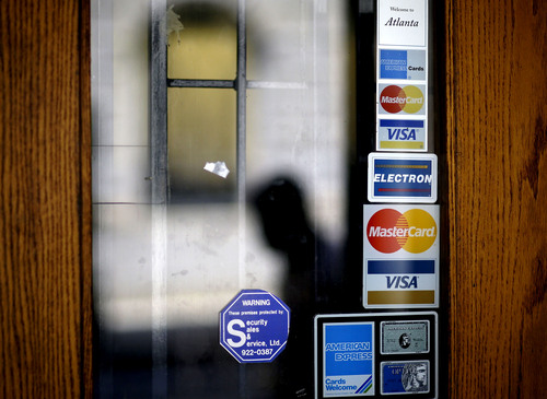 FILE - In this July 18, 2012 file photo, credit card logos are seen on a downtown storefront as a pedestrian passes in Atlanta. Household debt surged at an unprecedented rate in the five years before the financial crisis. In the U.S., the U.K. and France, it soared more than 50 percent per adult. For the world's top 10 economies, it jumped 34 percent. Then the financial crisis hit, and people slammed the brakes on borrowing. Debt per adult in the 10 countries fell 1 percent in the 41⁄2 years after 2007. Economists say debt hasn't fallen in sync like that since the end of World War II.  (AP Photo/David Goldman, File)