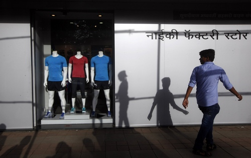 FILE - In this Aug. 31, 2013, file photo, an Indian man walks in front of a factory outlet store in Mumbai, India. Despite a growing middle class, Indians have dumped 15 percent of their stock holdings in the five years after the financial crisis. (AP Photo/Rajanish Kakade, File)
