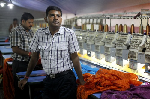 In this Sept. 2, 2013 photo,Pradeep Kumar Yadav stands inside his embroidery factory in Varanasi, India. Despite nearly two decades of rapid economic growth, most Indians are risk averse and do not own stocks. (AP Photo/ Rajesh Kumar Singh)