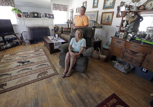In this Aug. 27, 2013 photo, Madeleine and Jerry Bosco pose for a photo in their living room, filled with mostly inherited or thrift shop furnishings and a hardwood floor in need of refinishing or replacement, in the Tujunga area of Los Angeles. During the recession, Jerry's pay was cut 15 percent, and their home lost some of its value. Five years later, they're still cutting back on necessities such as food, utilities, home repairs and new appliances, as well as extras such as weekend trips and dinners out. (AP Photo/Reed Saxon)