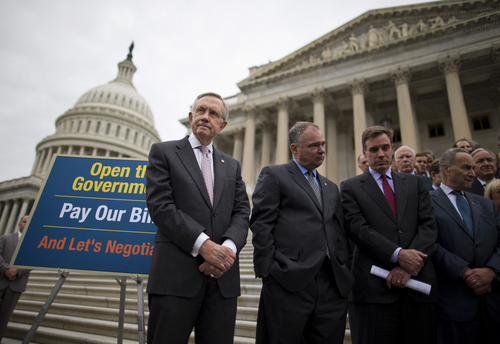 From left, Senate Majority Leader Harry Reid of Nev., Sen. Tim Kaine, D-Va., Sen. Mark Warner, D-Va., Sen. Charles Schumer, D-N.Y., and others stand on the Senate steps on Capitol Hill in Washington, Wednesday, Oct. 9, 2013, during a news conference on the ongoing budget battle. President Barack Obama was making plans to talk with Republican lawmakers at the White House in the coming days as pressure builds on both sides to resolve their deadlock over the federal debt limit and the partial government shutdown.  (AP Photo/ Evan Vucci)
