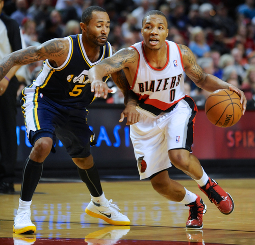 Utah Jazz' Mo Williams (5) defends a drive by Portland Trail Blazers' Damian Lillard (0) during the second half of an NBA preseason basketball game in Portland, Ore., Monday, Oct., 22, 2012. Lillard had 21 points as the Trail Blazers beat the Jazz 120-114. (AP Photo/Greg Wahl-Stephens)