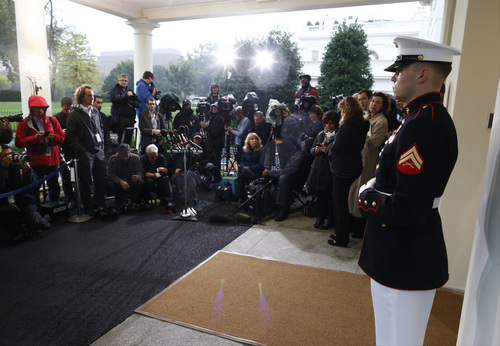 A Marine honor guard stands watch as reporters wait for comment from Republican congressmen who are meeting with President Barack Obama regarding the government shutdown and debt ceiling, at the West Wing at the White House in Washington, Thursday, Oct. 10, 2013. The lawmakers, including House Speaker John Boehner of Ohio, left the White House without speaking to waiting reporters. (AP Photo/Charles Dharapak)