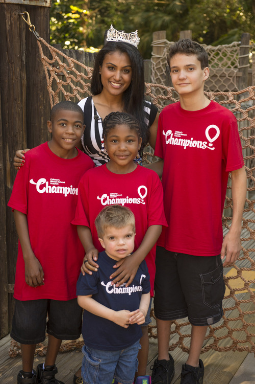 """Miss America 2014 Nina Davuluri of Syracuse, NY, joins members of the 2013 """"Champions of Children's Miracle Network (CMN) Hospitals"""" Oct. 10, 2013 at the Magic Kingdom at Walt Disney World Resort in Lake Buena Vista, Fla.  Davuluri and the CMN Champions are at Walt Disney World for the 30th anniversary of the Children's Miracle Network Celebration.  The Celebration was founded by actor John Schneider and singer/actress Marie Osmond. The Walt Disney Company has been a partner with Children's Miracle Network Hospitals since 1987 and the Walt Disney World Resort serves as the host for the annual Celebration event. (AP Photo/Walt Disney World Resort, Kent Phillips)"""