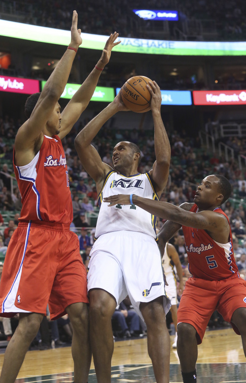 Utah Jazz's Brian Cook, middle, tries to take a shot between Los Angeles Clippers' Ryan Hollins, left, and Maalik Wayns during the second half during an NBA preseason basketball game Saturday, Oct. 12, 2013, in Salt Lake City. The Clippers won 106-74. (AP Photo/Kim Raff)