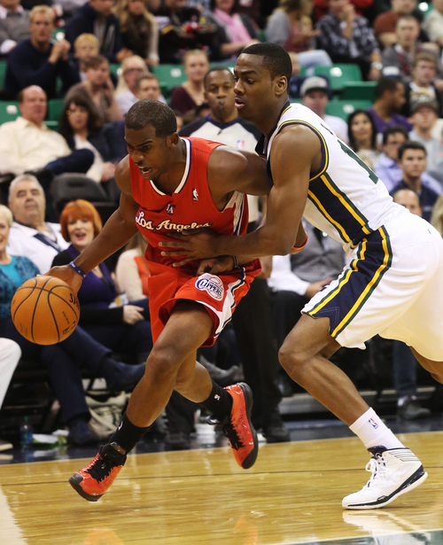 Los Angeles Clippers' Chris Paul, left, dribbles past Utah Jazz's Alec Burks, right, in the first quarter during an NBA preseason basketball game on Saturday, Oct. 12, 2013, in Salt Lake City. (AP Photo/Kim Raff)