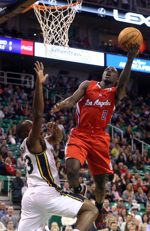 Los Angeles Clippers' Darren Collison (2) attempts a basket as Utah Jazz's Mike Harris, left, defends in the first quarter during an NBA preseason basketball game on Saturday, Oct. 12, 2013, in Salt Lake City. (AP Photo/Kim Raff)