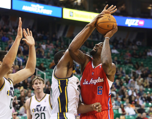 Los Angeles Clippers' DeAndre Jordan, right, attempts a field goal as he is defended by Utah Jazz's Enes Kanter, left, and Derrick Favors, center, in the first quarter during an NBA preseason basketball game on Saturday, Oct. 12, 2013, in Salt Lake City. (AP Photo/Kim Raff)