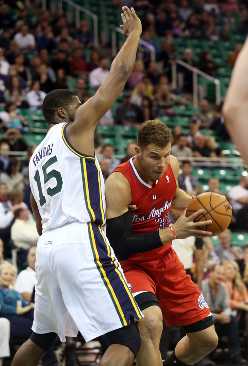 Utah Jazz's Derrick Favors (15) defends Los Angeles Clippers' Blake Griffin (32) who goes for a basket in the first quarter during an NBA preseason basketball game on Saturday, Oct. 12, 2013, in Salt Lake City. (AP Photo/Kim Raff)