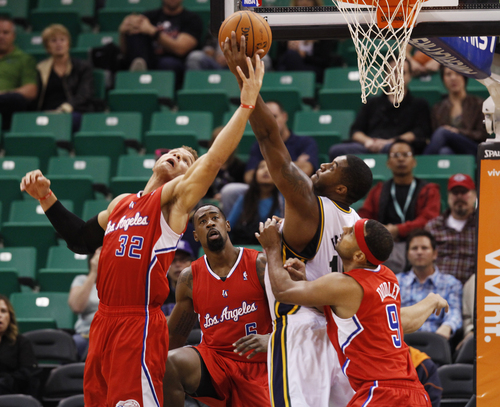 Los Angeles Clippers' Blake Griffin, left, and Utah Jazz's Derrick Favors, middle right, compete for a rebound in the first half during an NBA preseason basketball game Saturday, Oct. 12, 2013, in Salt Lake City.  (AP Photo/Kim Raff)