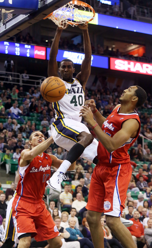 Utah Jazz's Jeremy Evans, center, dunks between Los Angeles Clippers' Lou Amundson, left, and Ryan Hollins during the second half during an NBA preseason basketball game Saturday, Oct. 12, 2013, in Salt Lake City. The Clippers won 106-74. (AP Photo/Kim Raff)