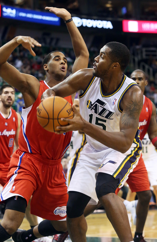 Utah Jazz's Derrick Favors, right, looks to pass the ball away from Los Angeles Clippers' Brandon Davies, left, in the second half of an NBA preseason basketball game Saturday, Oct. 12, 2013, in Salt Lake City. The Clippers won 106-74. (AP Photo/Kim Raff)