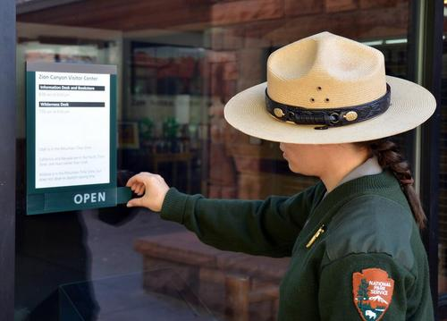 A park ranger changes the sign on the The Zion Canyon Visitor Center on Friday afternoon. (Courtesy Zion National Park on Twitter)