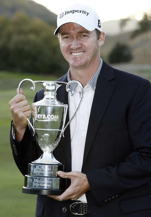 Jimmy Walker poses for photographs as he holds the trophy after winning the Frys.com Open golf tournament, Sunday, Oct. 13, 2013, in San Martin, Calif. (AP Photo/Tony Avelar)