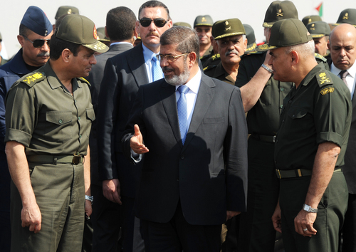 FILE - In this Wednesday, Oct. 10, 2012 file photo provided by the Egyptian Presidency, Egyptian President Mohammed Morsi, center, speaks with Minister of Defense, Lt. Gen. Abdel-Fattah el-Sissi, left, at a military base in Ismailia, Egypt. Washington's decision to withhold millions of dollars in mostly military aid to Egypt fuels anti-U.S. sentiment in the most populous Arab nation along with the perception that Washington supports Morsi, the Islamist president the military ousted in a July coup. Heightening those sentiments could boost the popularity of El-Sissi, whom the U.S. is trying to pressure to ensure a transition to democracy. (AP Photo/Egyptian Presidency, File)
