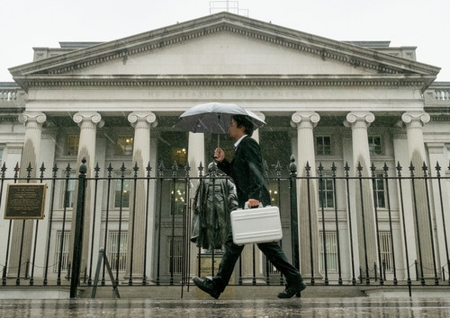In this Thursday, Oct. 10, 2013 photo, a pedestrian walks past the U.S. Treasury Building in Washington on a rainy day. The national debt actually reached the limit in May 2013. Since then, Treasury Secretary Jacob Lew has made accounting moves to continue financing the government without further borrowing. But Lew says those measures will be exhausted by Thursday, Oct. 17, 2013. The government will then have to pay its bills from its cash on hand — an estimated $30 billion — and tax revenue. (AP Photo/J. David Ake)