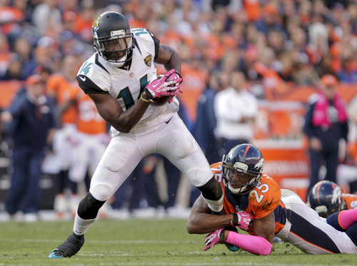 Jacksonville Jaguars wide receiver Justin Blackmon (14) tries to pull away from Denver Broncos cornerback Chris Harris (25) after catching pass in the fourth quarter of an NFL football game, Sunday, Oct. 13, 2013, in Denver. Denver won 35-19(AP Photo/Joe Mahoney)
