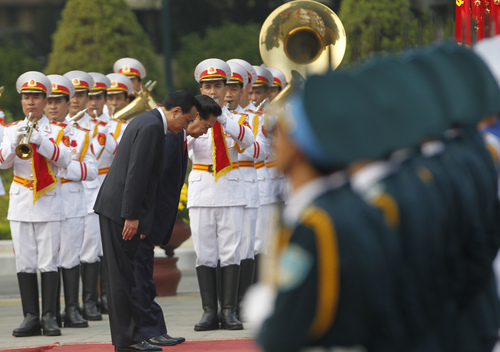 Chinese Primier Li Keqiang, left, and his Vietnamese counterpart Nguyen Tan Dung bow while reviewing the guard of honour during a welcoming ceremony at the Presidential Palace in Hanoi Sunday October 13, 2013. Li is in Hanoi on a three-day visit to Vietnam from October 13 to 15. (AP Photo/Kham)
