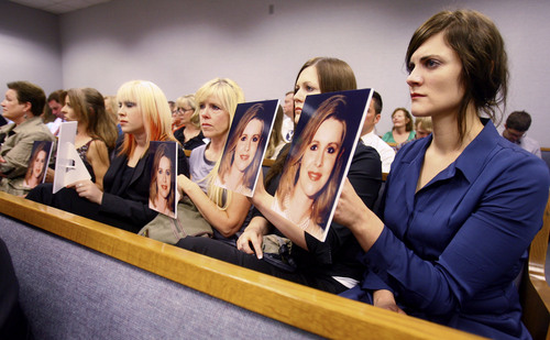 | Scott Winterton pool  Jill Harper-Smith, Linda Cluff, Alexis Somers and Rachel MacNeill hold up photos of Michele MacNeill facing Martin Joseph MacNeill as he makes his initial appearance Monday, Aug. 27, 2012 before Judge Samuel D. McVey in Provo.