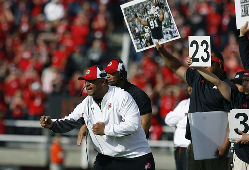 Scott Sommerdorf   |  The Salt Lake Tribune Utah defensive coordinator Kelani Sitake sends in signals during first half play. The picture being held above him is former Ute Sione Pouha during his playing time with the New York Jets. Utah upset #5 Stanford 27-21, Saturday, October 12, 2013.
