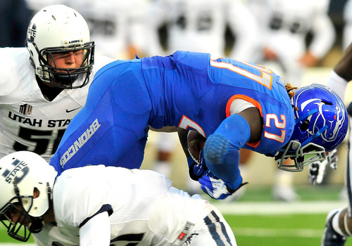 Boise State's Jay Ajayi (27) dives over Utah State's Brian Suite (21) during their game, Saturday, Oct. 12, 2013, in Logan, Utah. (AP Photo/Herald Journal, John Zsiray)