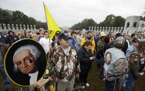 Noreen Grimm stands next to her husband David Grimm, both from Pittsburgh, Pa., holding a portrait of President George Washington during a rally at the World War II Memorial in Washington Sunday, Oct. 13, 2013. The rally was organized to protest the closure of the Memorial, subsequent to the shutdown, and lack of access to it by World War II veterans, who traveled there on Honor Flight visits. Leaders in the Senate have taken the helm in the search for a deal to end the partial government shutdown and avert a federal default. (AP Photo/Alex Brandon)