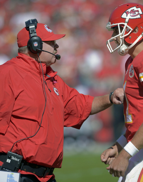Kansas City Chiefs coach Andy Reid, left, talks with quarterback Alex Smith during the first half of an NFL football game against the Oakland Raiders at Arrowhead Stadium in Kansas City, Mo., Sunday, Oct. 13, 2013. (AP Photo/Reed Hoffmann)