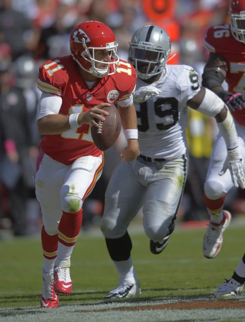 Kansas City Chiefs quarterback Alex Smith (11) runs from Oakland Raiders defensive end Lamarr Houston (99) during the second half of their NFL football game against the Oakland Raiders at Arrowhead Stadium in Kansas City, Mo., Sunday, Oct. 13, 2013. (AP Photo/Reed Hoffmann)