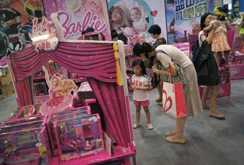 FILE - In this Thursday, July 25, 2013, file photo, women with their children visit Barbie toys on display for sale at the Kids Fun Expo in Beijing.  Mattel, which manufactures Barbie toys, reports quarterly earnings on Oct. 16, 2013. (AP Photo/Andy Wong, File)