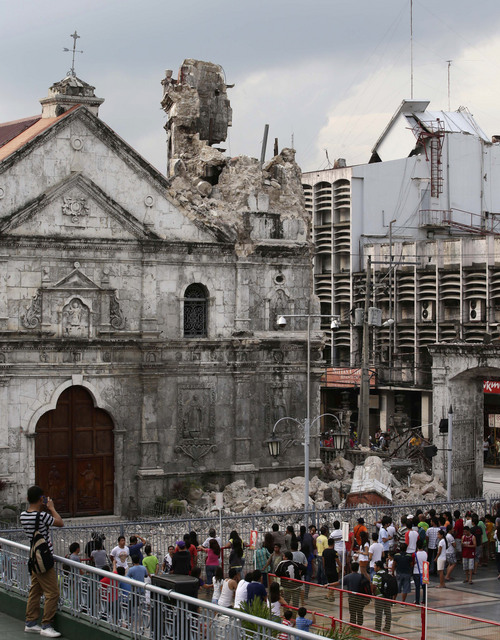 Residents look at the Basilica De Sto. Nino, or Basilica of the Holy Child, following a 7.2-magnitude earthquake that hit Cebu city in central Philippines Tuesday Oct. 15, 2013. The tremor collapsed buildings, cracked roads and toppled the bell tower of the Philippines' oldest church Tuesday morning, causing multiple deaths across the central region and sending terrified residents into deadly stampedes. (AP Photo/Bullit Marquez)