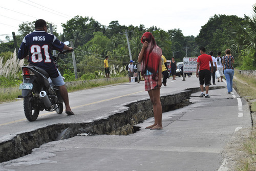 Residents walk along a damaged road following a 7.2-magnitude earthquake that hit Bohol, central Philippines, Tuesday, Oct. 15, 2013. The tremor collapsed buildings, cracked roads and toppled the bell tower of the Philippines' oldest church Tuesday morning, causing multiple deaths across the central region and sending terrified residents into deadly stampedes. (AP Photo)
