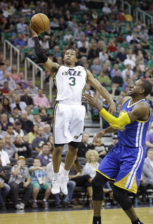FILE - This Oct. 8, 2013, file photo, Utah Jazz's Trey Burke (3) shoots as Golden State Warriors' Andre Iguodala, right, looks on in the second half during an NBA preseason basketball game, in Salt Lake City. Utah Jazz rookie Burke will undergo surgery on a broken finger on his shooting hand. Burke will have the surgery on Tuesday morning in Salt Lake City. Pins will be inserted to stabilize the point guard's right index finger, which he fractured during a 106-74 preseason loss to the Los Angeles Clippers on Saturday night. Team officials did not announce a timetable for Burke's return on Monday, but he is expected to miss anywhere from eight to 12 weeks while recovering from the operation. The former Michigan star was penciled in as a starter after the Jazz acquired his rights from the Minnesota Timberwolves in a draft night trade. (AP Photo/Rick Bowmer, File)
