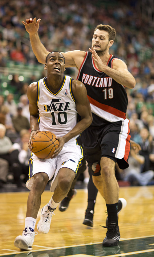 Lennie Mahler  |  The Salt Lake Tribune Alec Burks drives to the basket in front of Portland's Joel Freeland as the Utah Jazz face the Portland Trailblazers at EnergySolutions Arena on Wednesday, Oct. 16, 2013. Portland beat Utah 99-92.